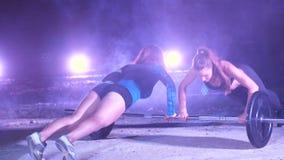 Duas meninas atléticas nos pares que fazem a força exercitam com um barbell, empurram levantam, na noite, no fumo claro, névoa, à video estoque