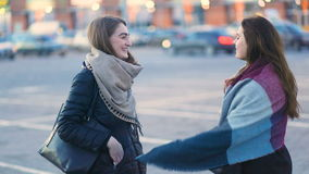 Duas meninas atrativas novas que riem e que sorriem na rua urbana na frente da construção enorme Came constante, mo lento vídeos de arquivo