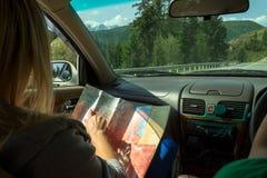 Duas meninas atrativas novas viajam pelo carro entre o cov das montanhas fotografia de stock
