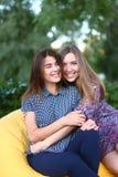 Duas meninas atrativas que sentam-se próximos um do outro na cadeira, smilin Foto de Stock