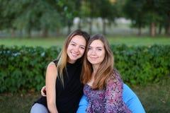 Duas meninas atrativas que sentam-se próximos um do outro na cadeira, smilin Imagem de Stock