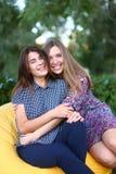 Duas meninas atrativas que sentam-se próximos um do outro na cadeira, smilin Imagens de Stock Royalty Free