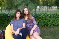 Duas meninas atrativas que sentam-se próximos um do outro na cadeira, smilin Fotografia de Stock Royalty Free