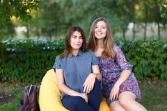 Duas meninas atrativas que sentam-se próximos um do outro na cadeira, smilin Fotos de Stock
