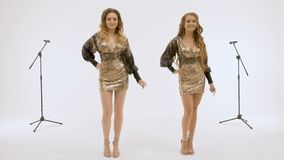 Duas meninas bonitas cantam e dançam no estúdio, em um fundo branco Disparando em uma vídeo clip vídeos de arquivo