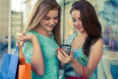 Duas meninas bonitas com sacos de compras e telefone celular coloridos Imagem de Stock