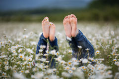 Duas meninas bonitas da criança estão encontrando-se para baixo com pés acima no campo da camomila Imagens de Stock Royalty Free