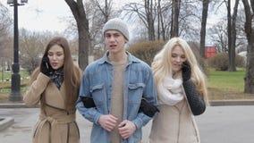 Duas meninas bonitas e um homem novo estão andando ao longo da rua Louro e morena falar no telefone, indivíduo faz filme