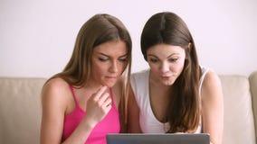 Duas meninas bonitas entusiasmado que usam o portátil, comprando em linha na venda vídeos de arquivo