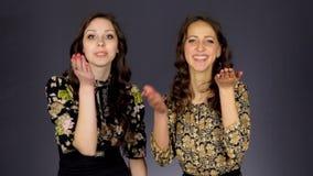 Duas meninas bonitas enviam um beijo do ar video estoque