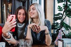Duas meninas bonitas estão fazendo o selfie em um café e em um sorriso Foto de Stock Royalty Free