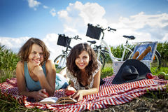 Duas meninas bonitas fazem um piquenique, lendo um livro foto de stock