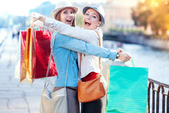 Duas meninas bonitas felizes com abraço dos sacos de compras na cidade Foto de Stock Royalty Free