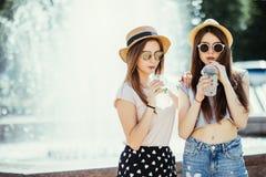 Duas meninas bonitas felizes com os equipamentos do verão que têm o divertimento na rua com cocltails no dia de verão ensolarado  fotografia de stock royalty free