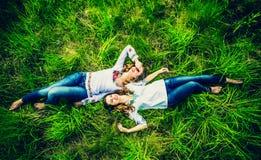 Duas meninas bonitas felizes que encontram-se na grama verde Imagens de Stock Royalty Free