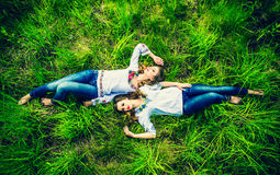 Duas meninas bonitas felizes que encontram-se na grama verde Fotos de Stock Royalty Free