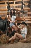 Duas meninas bonitas, louro e morena, com olhar do país, dispararam dentro no estilo estável, rústico Mulheres atrativas com chap imagem de stock