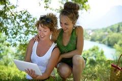 Duas meninas bonitas na grama com uma tabuleta digital Fotografia de Stock Royalty Free