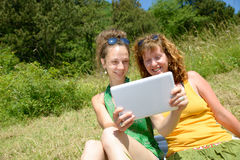 Duas meninas bonitas na grama com uma tabuleta digital Fotos de Stock Royalty Free
