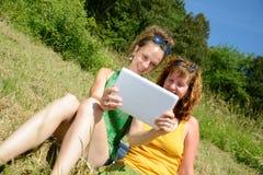 Duas meninas bonitas na grama com uma tabuleta digital Foto de Stock