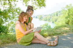 Duas meninas bonitas na grama com uma tabuleta digital Imagens de Stock Royalty Free