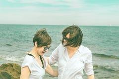 Duas meninas bonitas na praia que sorriem e que olham se Fotos de Stock Royalty Free