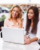 Duas meninas bonitas no café com portátil Fotografia de Stock