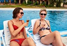 Duas meninas bonitas no champanhe bebendo do biquini Imagens de Stock