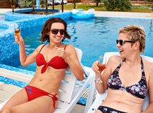 Duas meninas bonitas no champanhe bebendo do biquini Imagens de Stock Royalty Free