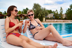 Duas meninas bonitas no champanhe bebendo do biquini Imagem de Stock