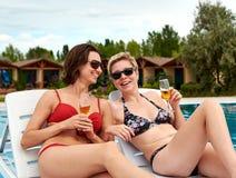 Duas meninas bonitas no champanhe bebendo do biquini Fotos de Stock