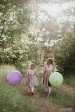 Duas meninas bonitas no ver?o em um parque com os bal?es nas m?os Menina feliz com bal?es imagens de stock