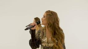 Duas meninas bonitas nos vestidos brilhantes que dançam e que cantam no estúdio em um fundo branco video estoque