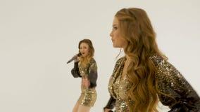 Duas meninas bonitas nos vestidos brilhantes que dançam e que cantam no estúdio em um fundo branco filme