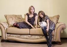 Duas meninas bonitas nos vestidos que sentam-se em um sofá Fotografia de Stock