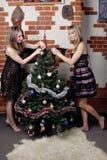 Duas meninas bonitas novas decoram a árvore de Natal Fotografia de Stock