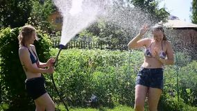Duas meninas bonitas novas derramam-se fora da mangueira de jardim em um gramado verde no dia ensolarado do verão Louro e moreno  video estoque