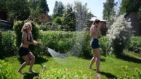 Duas meninas bonitas novas derramam-se fora da mangueira de jardim em um gramado verde no dia ensolarado do verão Louro e moreno  filme