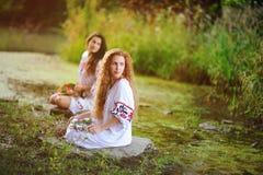 Duas meninas bonitas novas na camisa branca com o ornamento floral com as grinaldas em suas mãos que sentam-se no fundo de Fotografia de Stock