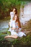 Duas meninas bonitas novas na camisa branca com o ornamento floral com as grinaldas em suas mãos que sentam-se no fundo de Fotografia de Stock Royalty Free