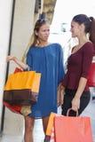 Duas meninas bonitas novas que criticam a janela de loja Foto de Stock