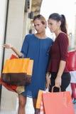 Duas meninas bonitas novas que criticam a janela de loja Fotos de Stock Royalty Free