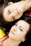 Duas meninas bonitas que encontram-se na grama. Fotos de Stock