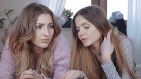Duas meninas bonitas que falam ao encontrar-se na cama video estoque