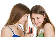 Duas meninas bonitas que lêem SMS no telefone móvel Imagem de Stock Royalty Free