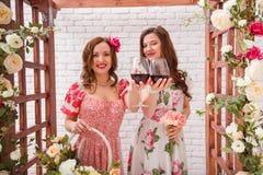 Duas meninas bonitas vestiram-se nos vestidos do verão que levantam perto de um arco da flor com vidros do vinho tinto nas mãos Foto de Stock Royalty Free