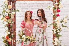 Duas meninas bonitas vestiram-se nos vestidos do verão que levantam perto de um arco da flor com vidros do vinho tinto nas mãos Fotos de Stock Royalty Free