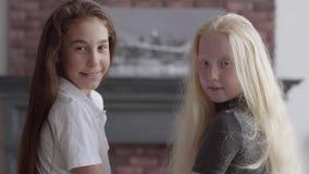 Duas meninas bonitos com o cabelo bonito longo que senta-se perto de se na sala de visitas Conceito da amizade carefree video estoque