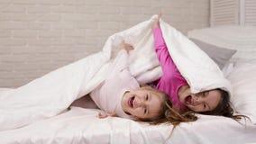Duas meninas bonitos das crian?as pequenas cobrem com a cobertura filme