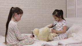 Duas meninas bonitos das crian?as que jogam o doutor com urso de peluche video estoque
